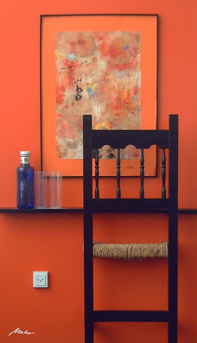 Conceptual assemblage work of orange background where you can see a  nebula, bottles, glasses and the back of a chair